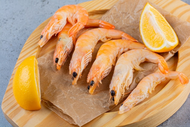 A wooden bowl of delicious shrimps with sliced lemon on a stone surface