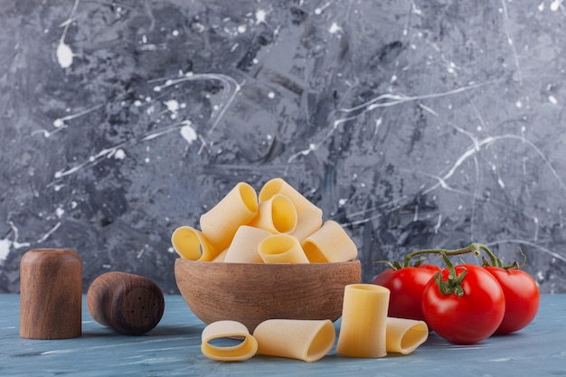 A wooden bowl of dry raw tube pasta with fresh red tomatoes and spices on a blue table .