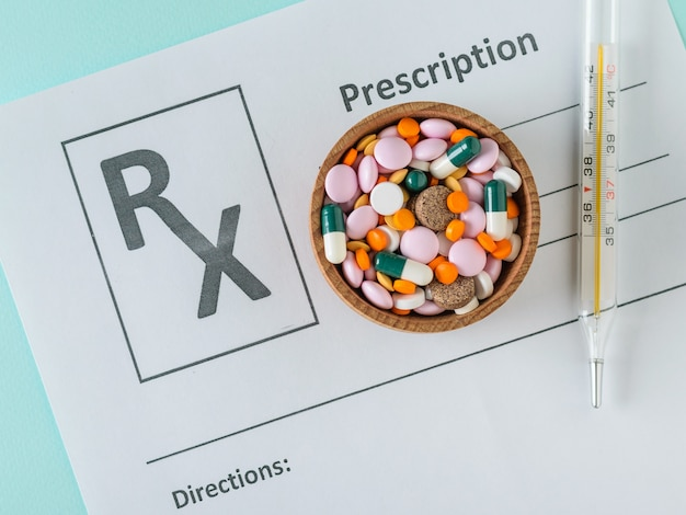 Wooden bowl filled with multi-colored tablets and thermometer on a sheet with prescription medication.
