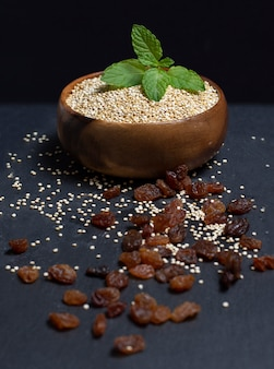 Wooden bowl filled with quinoa on black