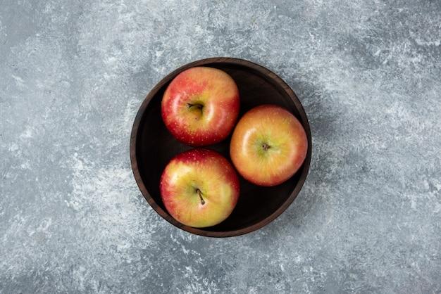 Ciotola di legno di mele fresche luminose sulla superficie in marmo.
