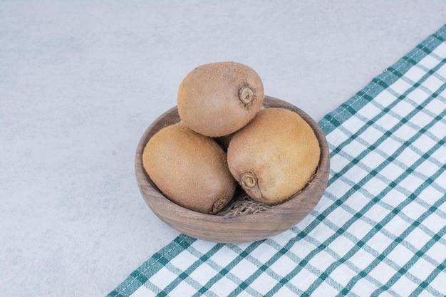 A wooden bowl of fresh kiwi on white background. high quality photo