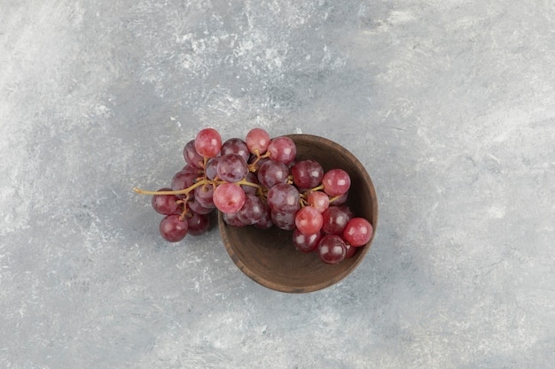 Wooden bowl of fresh red grapes on marble surface.