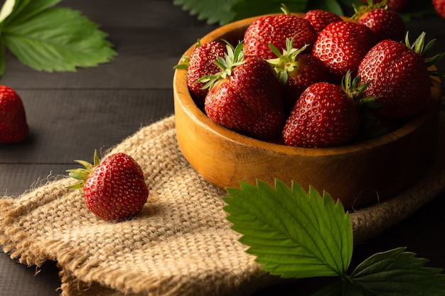 A wooden bowl of fresh red ripe strawberries on a black wooden surface