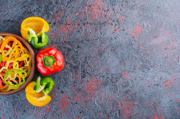 Wooden bowl full of chopped colorful peppers on marble surface