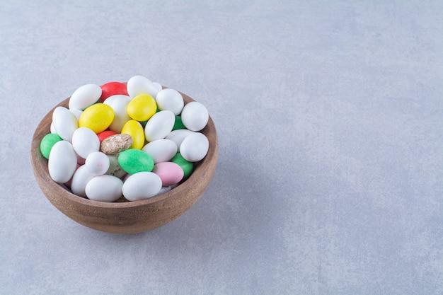 Una ciotola di legno piena di caramelle colorate di fagioli su sfondo grigio. foto di alta qualità