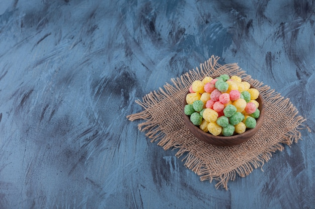 Wooden bowl full of colorful cereal balls on blue background.