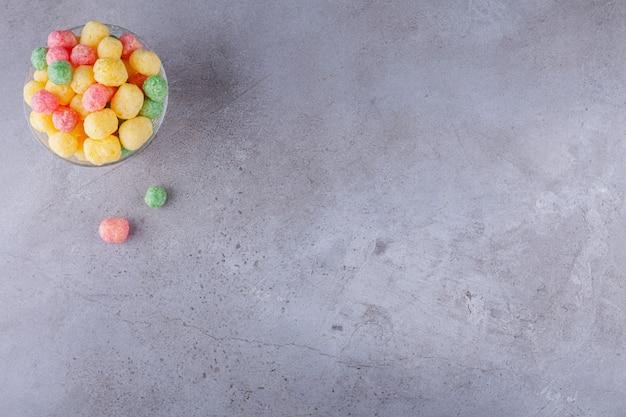 Ciotola di legno piena di palline di cereali colorate su sfondo blu.
