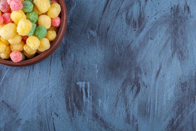 Ciotola di legno piena di palline di cereali colorate sul blu.