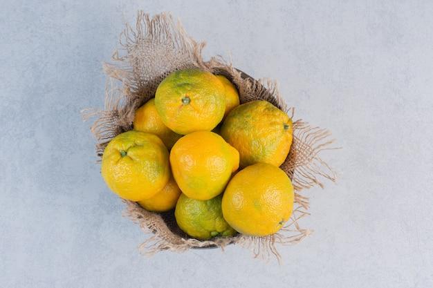 Ciotola di legno piena di mandarini freschi.