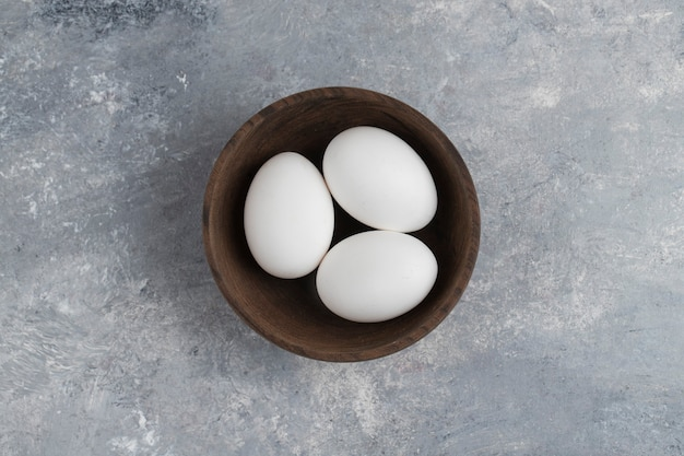 A wooden bowl full of fresh white chicken eggs on a marble background .
