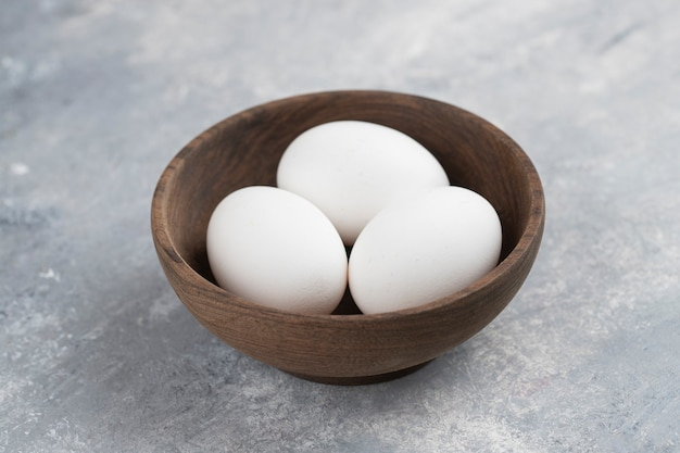 A wooden bowl full of fresh white chicken eggs on a marble .