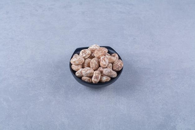Una ciotola di legno piena di cereali sani su una superficie grigia