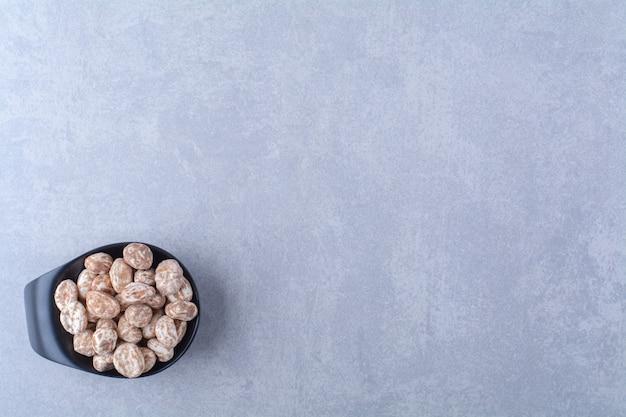 Una ciotola di legno piena di cereali sani sul tavolo grigio.