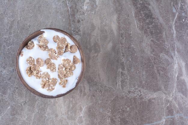Una ciotola di legno piena di cereali sani con latte per colazione.