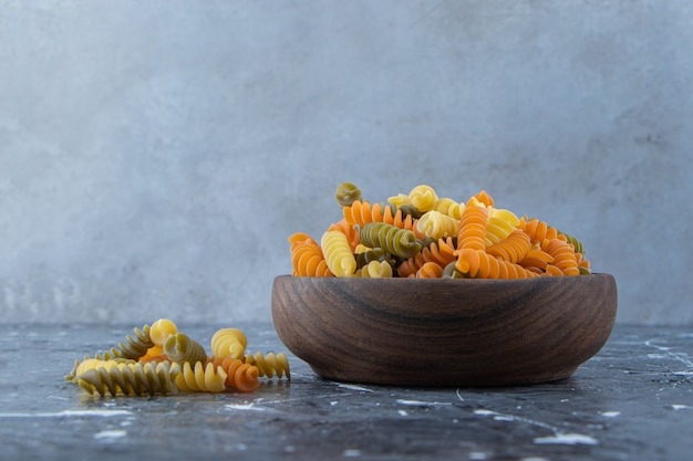 A wooden bowl full of multi colored macaroni on a gray background .