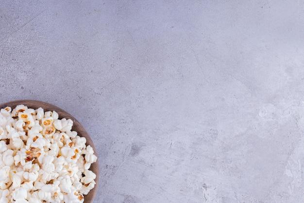 Деревянная миска, полная хрустящего попкорна на мраморном фоне. фото высокого качества