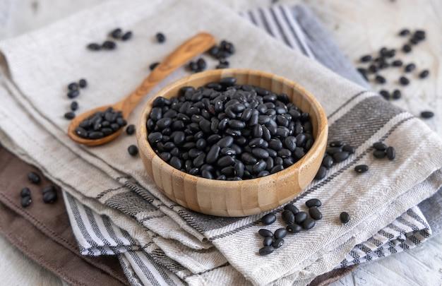 Деревянная миска, полная сушеных черных бобов с деревянной ложкой на кухонных полотенцах на деревянном столе крупным планом. здоровое питание и вегетарианская концепция. традиционный латиноамериканский кузен ингредиент