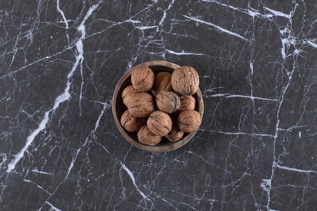 Деревянная миска, полная свежих грецких орехов в скорлупе на мраморе.