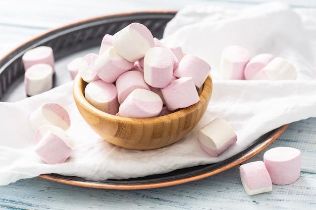 ピンクと白のマシュマロがいっぱい入った木製のボウル。白いテーブルクロス、暗いトレイ、白い木製のテーブルの上に散らばっています。
