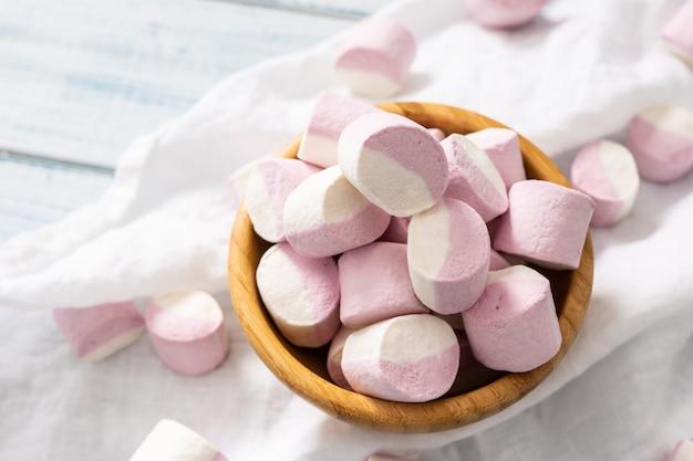 ピンクと白のマシュマロがいっぱい入った木製のボウル。白いテーブルクロスの上に散らばっています。
