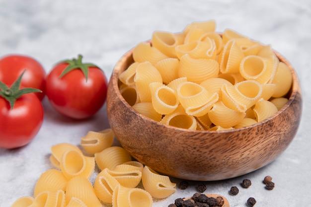 요리하지 않은 파스타 conchiglie의 전체 나무 보 울 대리석 배경에 배치합니다. 고품질 사진