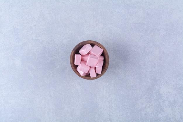 Una ciotola di legno piena di pasticceria dolce rosa pastila.
