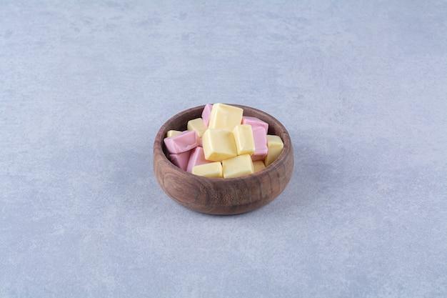 Una ciotola di legno piena di dolciumi rosa