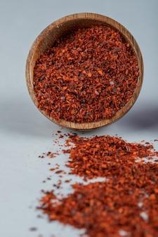 Una ciotola di legno piena di pepe rosso su una superficie bianca.