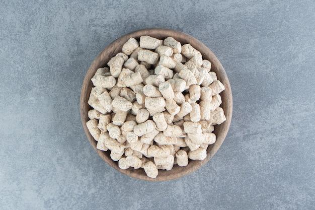 Una ciotola di legno piena di cereali croccanti di segale.