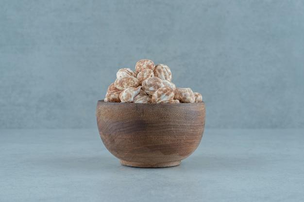 Una ciotola di legno piena di pan di zenzero dolce e delizioso su superficie bianca white