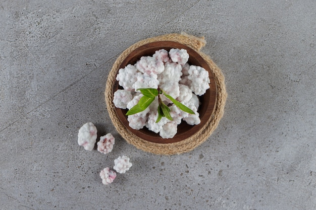 Una ciotola di legno piena di dolci caramelle bianche con foglie di menta su un tavolo di pietra.