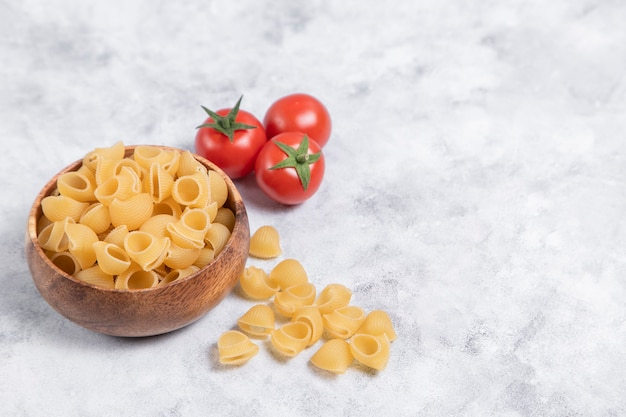 Wooden bowl full of uncooked pasta conchiglie placed on marble background . high quality photo