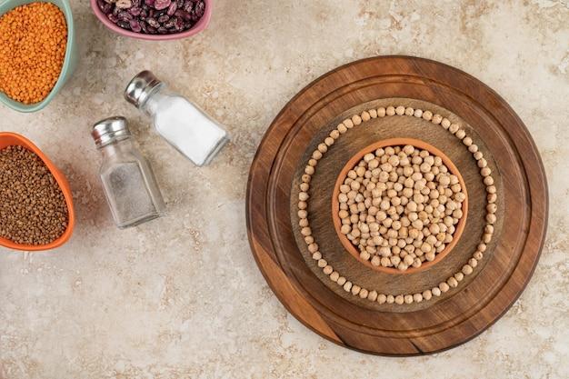 Una ciotola di legno piena di piselli non preparati con spezie e fagioli.