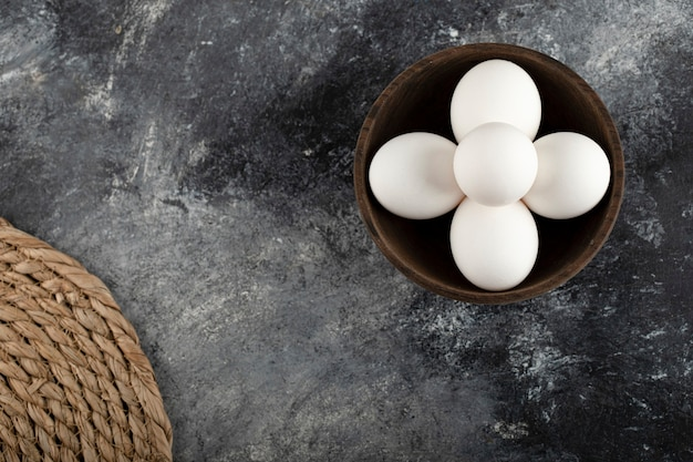 A wooden bowl full of white raw chicken eggs .
