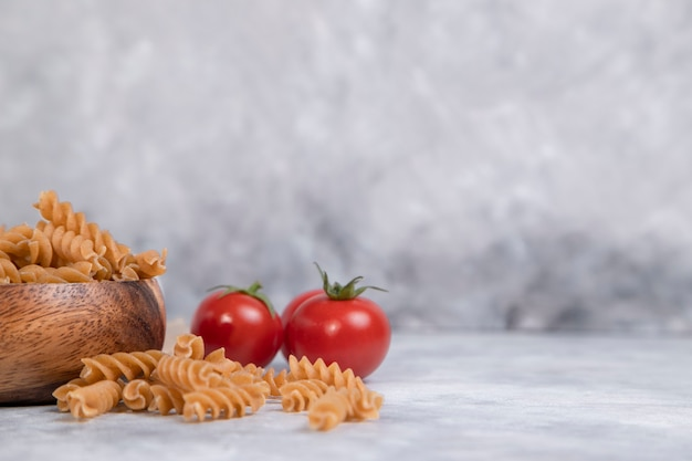 Wooden bowl full of wholegrain raw pasta placed on marble table .
