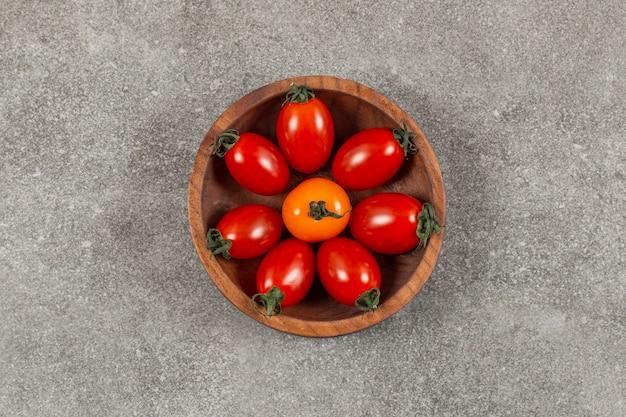 Ciotola di legno piena di pomodorini.