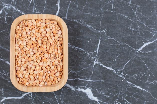 黒い石の上に乾燥したエンドウ豆でいっぱいの木製のボウル。