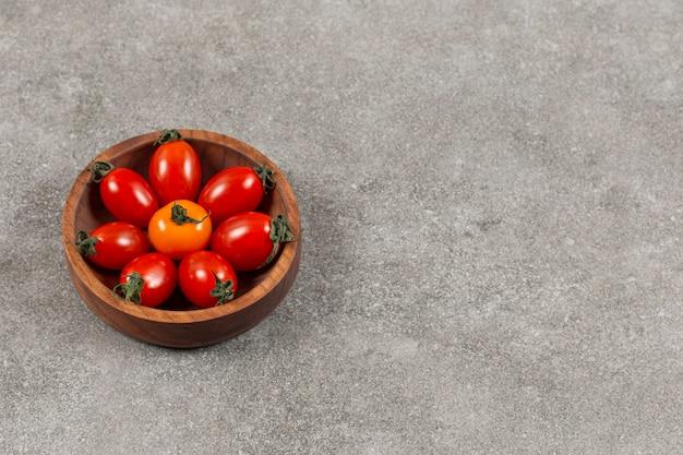 Ciotola di legno piena di pomodorini rossi.