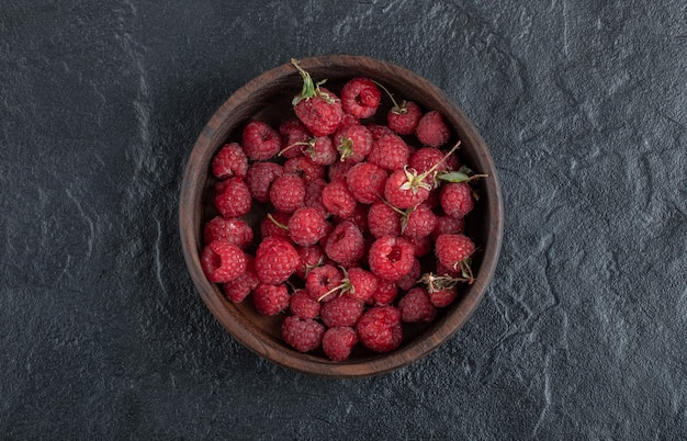 Wooden bowl of healthy red raspberries placed on marble surface