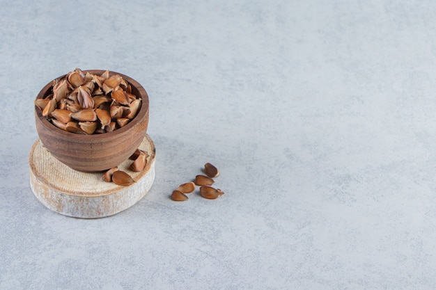 Wooden bowl of many crunchy seeds on stone background.