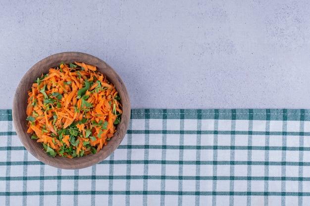 대리석 바탕에 식탁보에 당근 샐러드의 나무 그릇. 고품질 사진