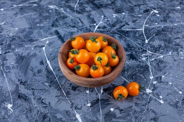 대리석에 체리 신선한 토마토의 나무 그릇입니다.