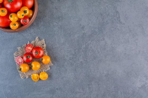 Деревянная миска с красочными органическими помидорами на каменной поверхности