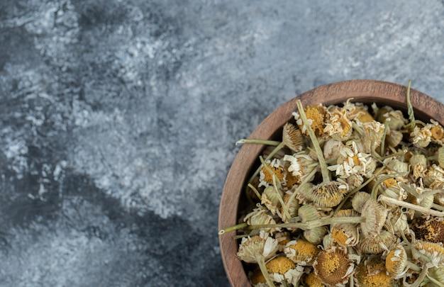 大理石のテーブルの上の乾燥カモミールの木製ボウル。
