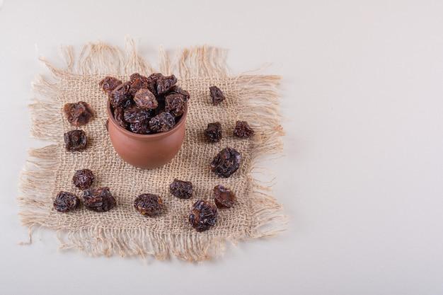 白い背景の上に置かれたプルーンフルーツの木製ボウル。高品質の写真