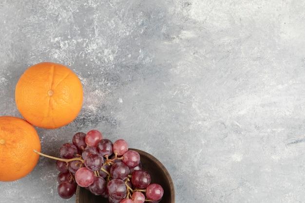 大理石の表面に新鮮な赤ブドウとオレンジの木製ボウル。