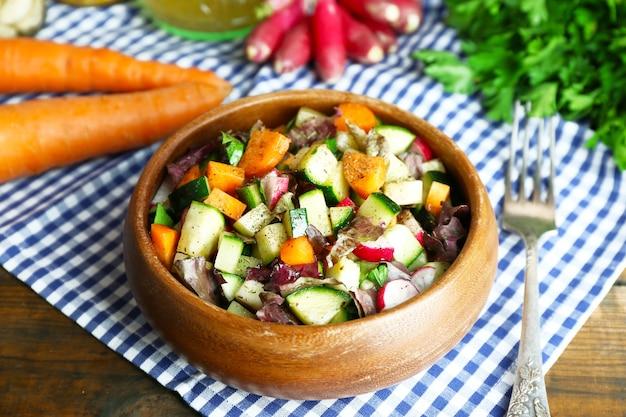 ナプキン、クローズアップの新鮮な野菜サラダの木製ボウル