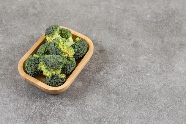 石のテーブルの上の健康的な新鮮なブロッコリーの木製ボウル。