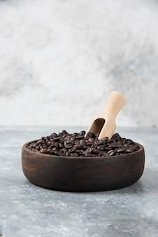 Деревянная миска среднего обжаренного кофе с ложкой на мраморной поверхности.